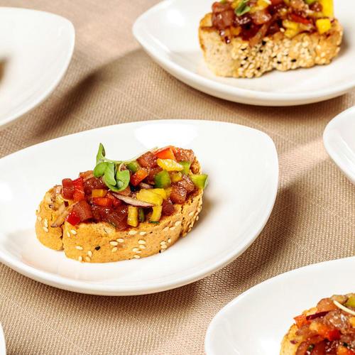 סביצ'ה טונה אדומה מוגש עם ירקות שורש צבעוניים, ויניגרט שמן שומשום אסיאתי על מצע קרוסטיני ואיולי שום קונפי